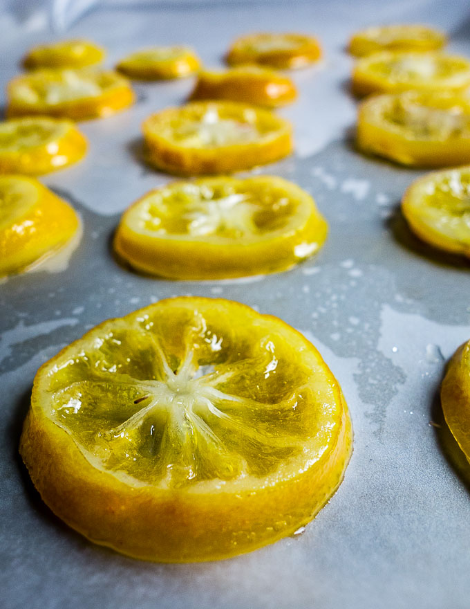 freshly candied lemon slices drying on baking sheet