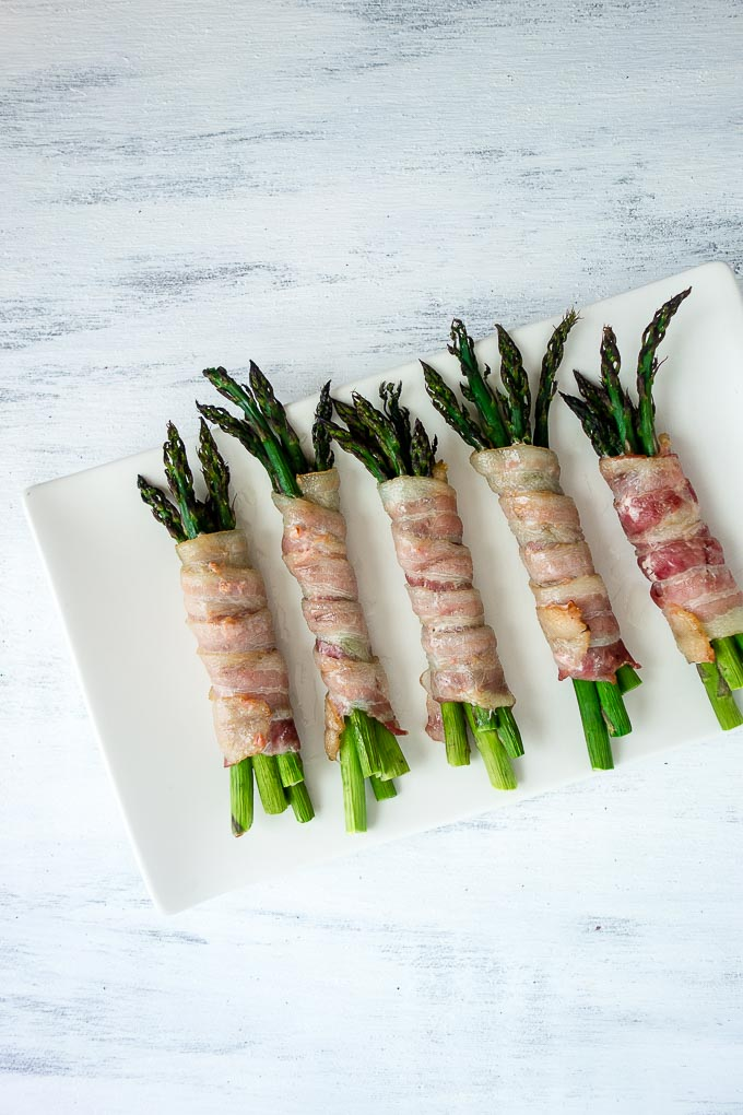 oven baked bacon wrapped asparagus on a plate