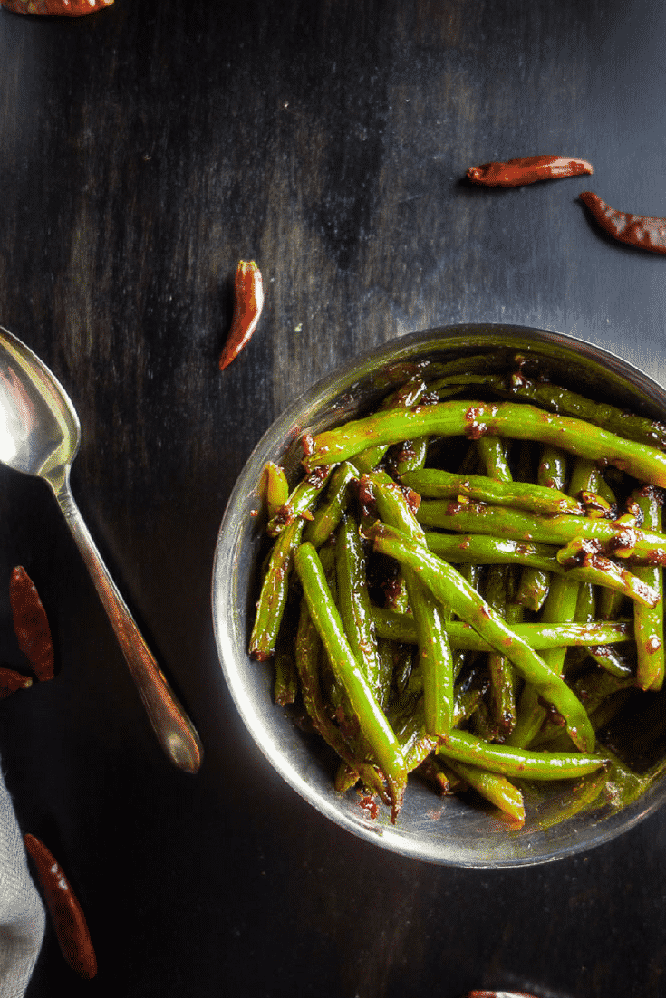 These tender spicy stir fried Sichuan green beans combine chili garlic sauce with a splash of soy sauce, minced garlic and ginger make for a perfect umami flavor.easy chinese sichuan green beans | szechuan green beans | spicy chinese green beans | stir fry green beans | Sichuan style green beans | chinese takeout recipes | chinese recipes | green bean recipes | fried spicy green beans | sichuan dry fried green beans
