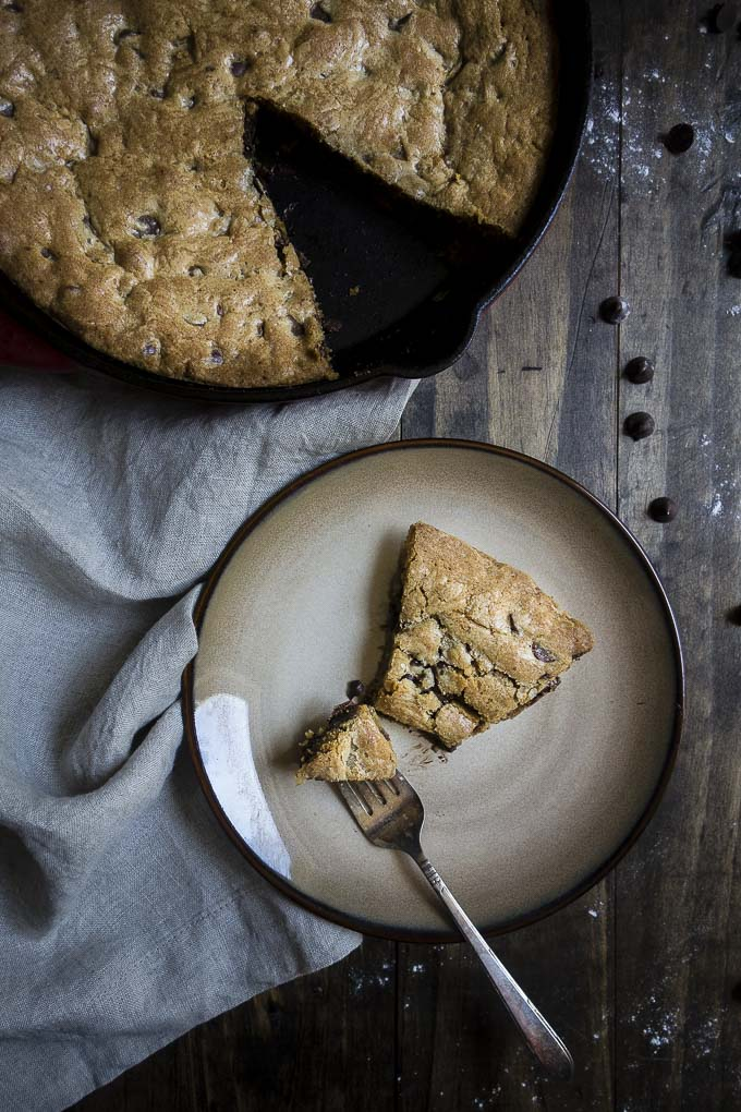 deep dish chocolate chip cookie pie on a plate and in a skillet