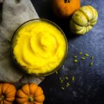 homemade pumpkin puree in a bowl with mini pumpkin on side