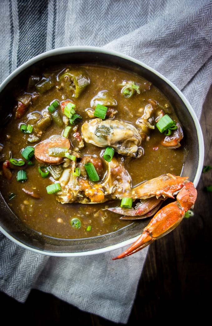 louisiana seafood gumbo with okra, seafood and sausage in roux in a bowl with crab claw