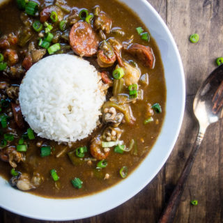 lousiana seafood gumbo with okra, seafood and sausage in roux in a bowl with rice