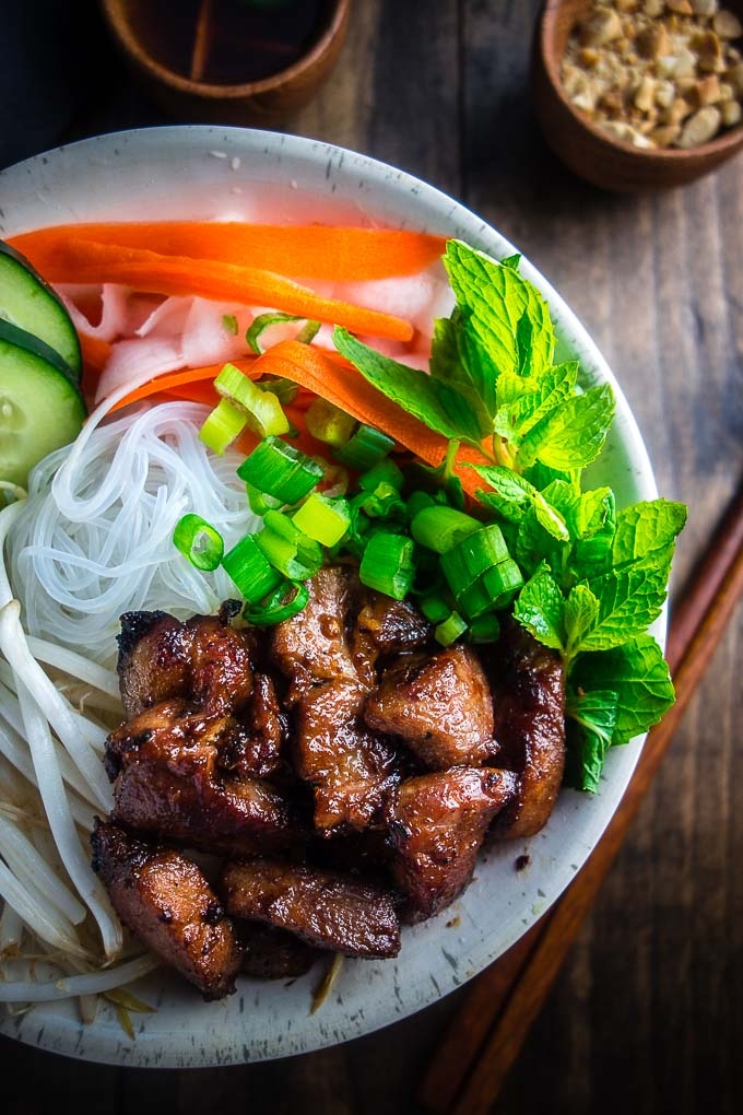 vietnamese pork in a bowl with noodles fresh herbs and carrots