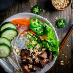 vietnamese pork noodle bowl with fresh veggies and herbs