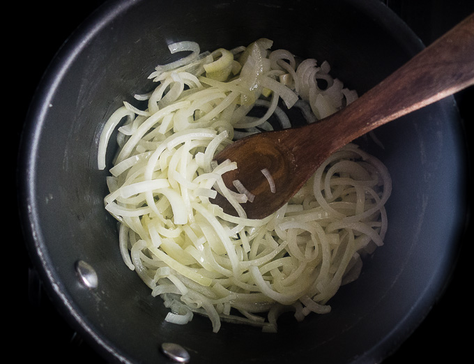 sliced onions in a saucepan with wooden spoon