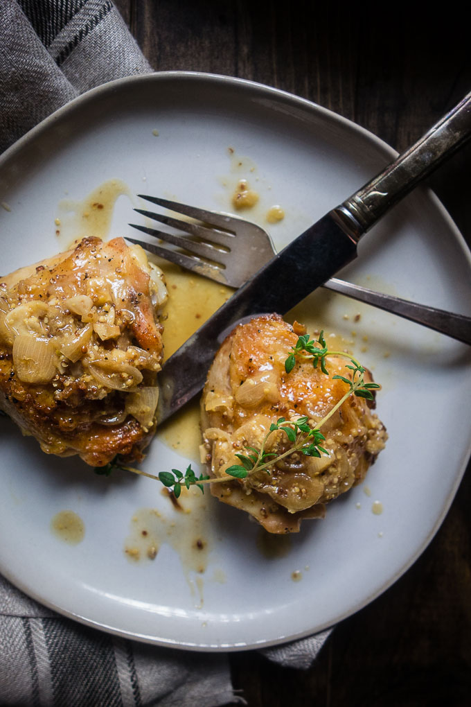 chicken thighs in white wine mustard sauce on a plate with fork and kmife