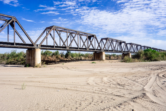 a railroad bridge over sandy river bed, roadtrip from san diego to tucson