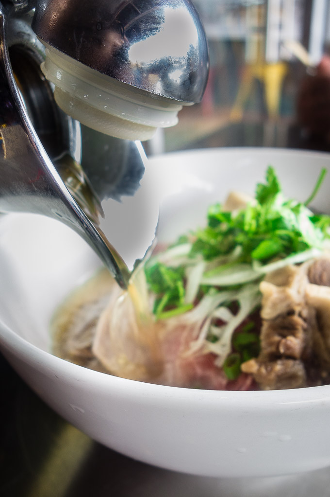 broth being poured into a bowl of meat and noodles