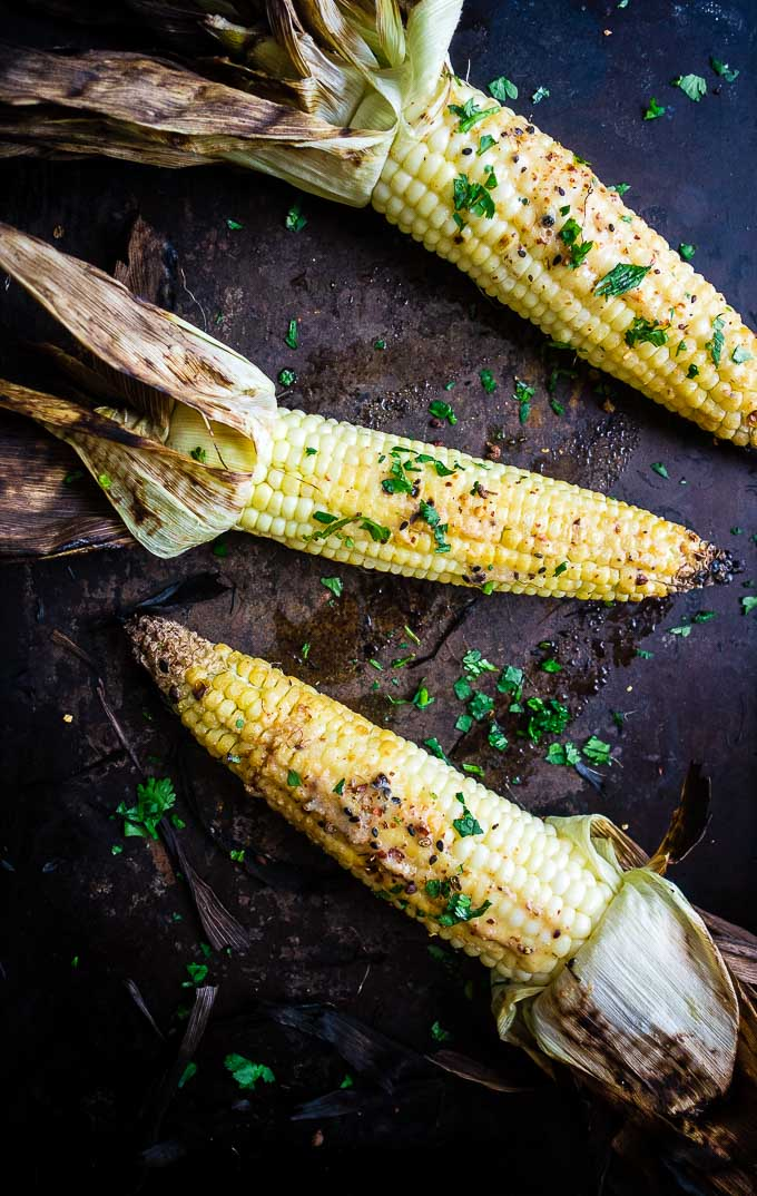 grilled corn on the cob on a platter with seasoning