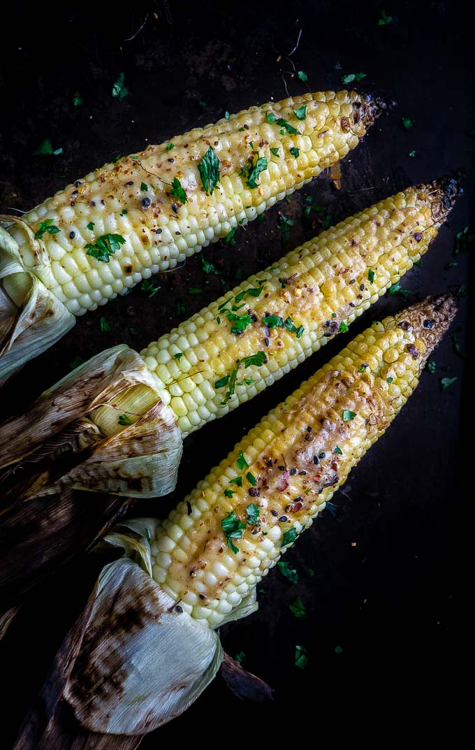grilled corn on a plate with cilantro