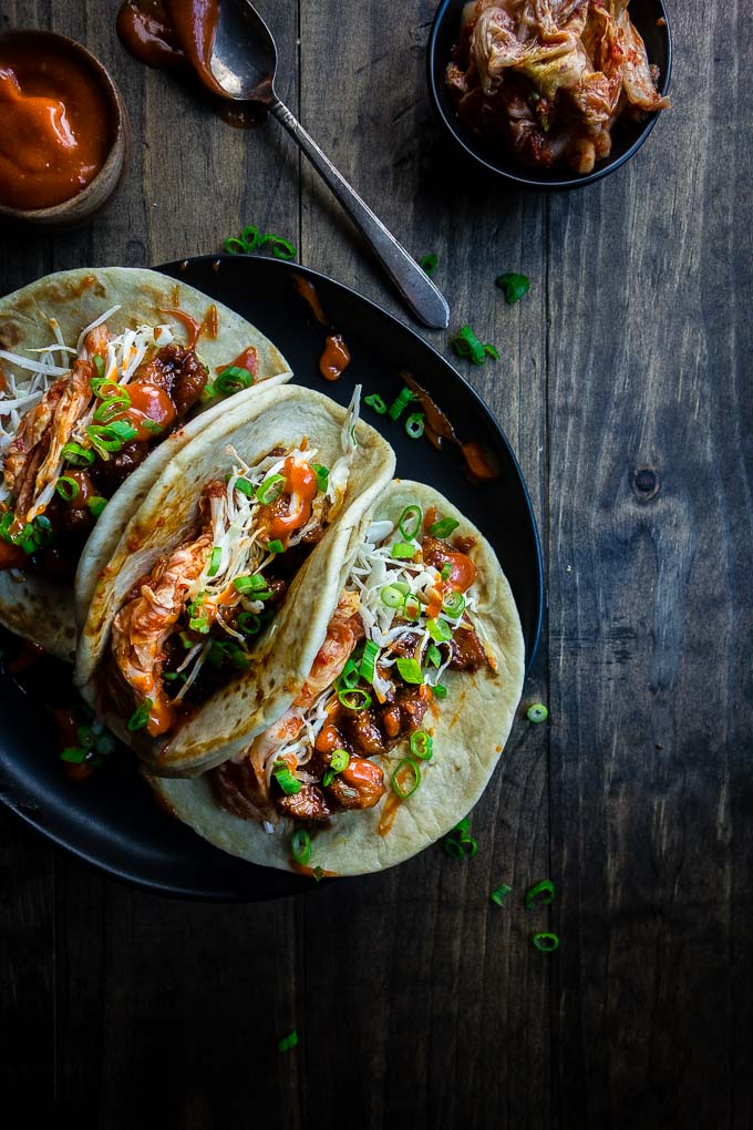 3 spicy pork tacos on a plate, meat in tortillas with vegetables