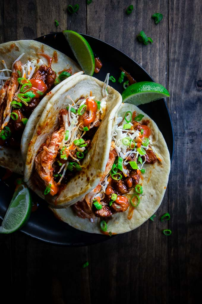 3 spicy pork tacos on a plate, meat in tortillas with vegetables with limes