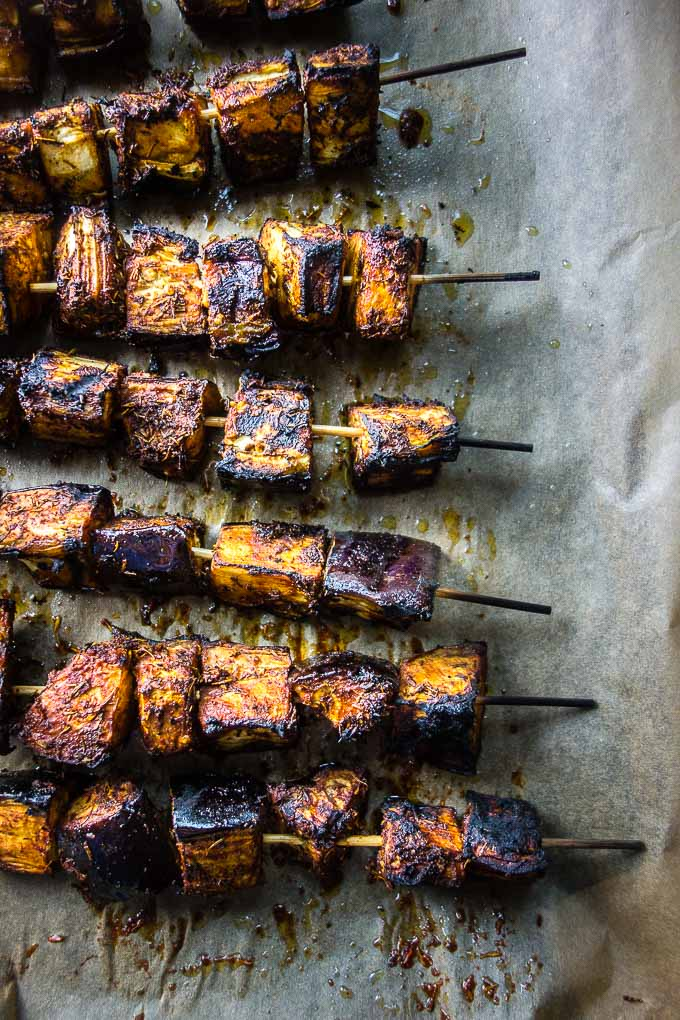 skewers of grilled eggplant on a baking sheet