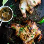 2 grilled cornish game hens covered in sauce and cilantro with lime