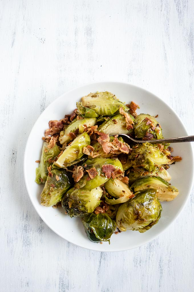 brussels sprouts and bacon in a bowl with a spoon