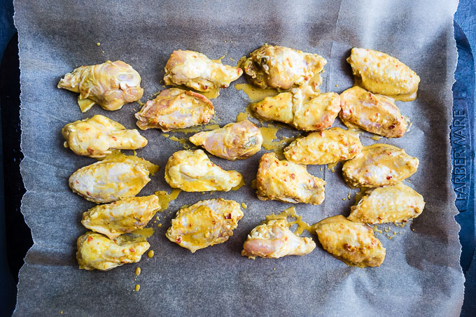 chicken wings on a baking sheet lined with parchment paper