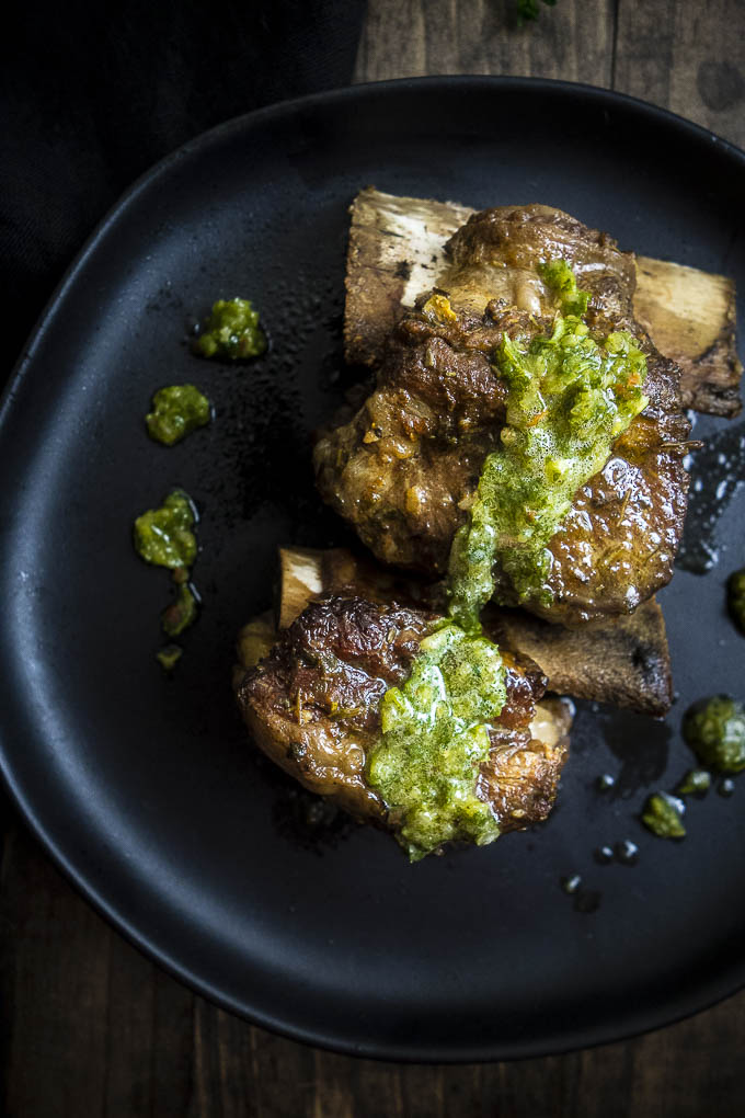 instant pot braised beef short ribs with chimuchurri sauce on a plate