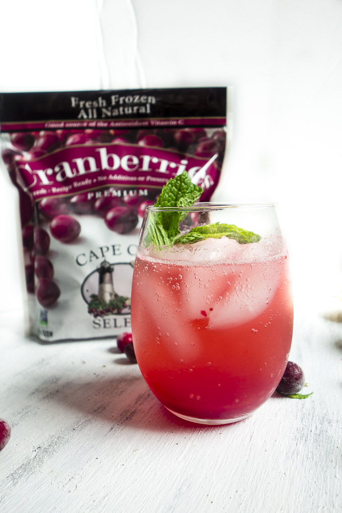 aprkling cranberry lemonade with bag of cranberries and fresh mint