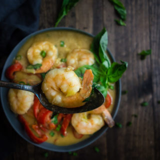 shrimp on a spoon with background bowl of thai green curry and vegetables