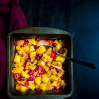 a pan of cranberry roasted butternut squash with a spoon