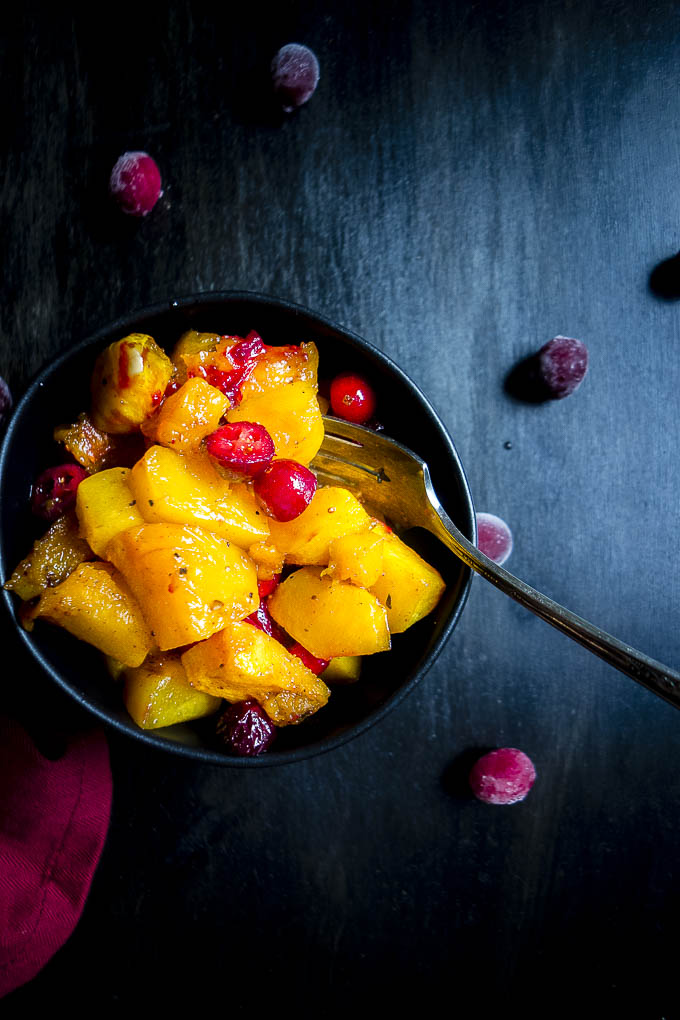 a bowl of cranberry roasted butternut squash with a fork