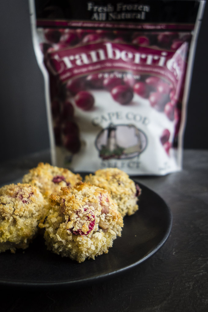 cranberry stuffing balls on a plate in front of a bag of frozen cranberries