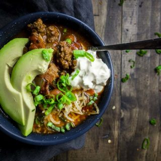 bowl of smoky beef and poblano chili with spoon and sour cream