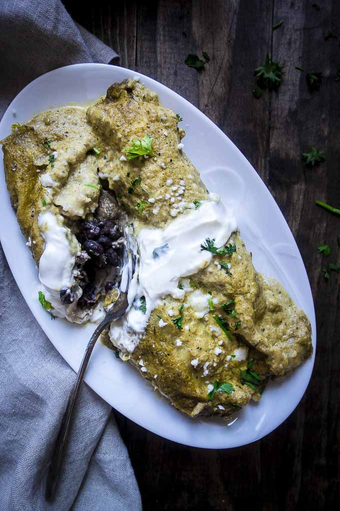 Plate of brazilian pulled pork enchiladas with crema