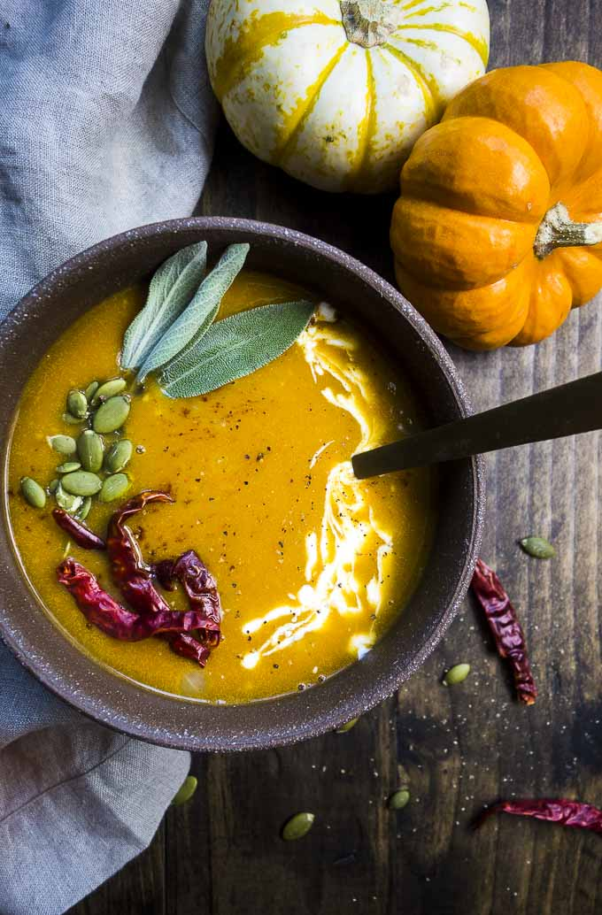 close up of spicy pumpkin soup with pumpkin seeds and sage