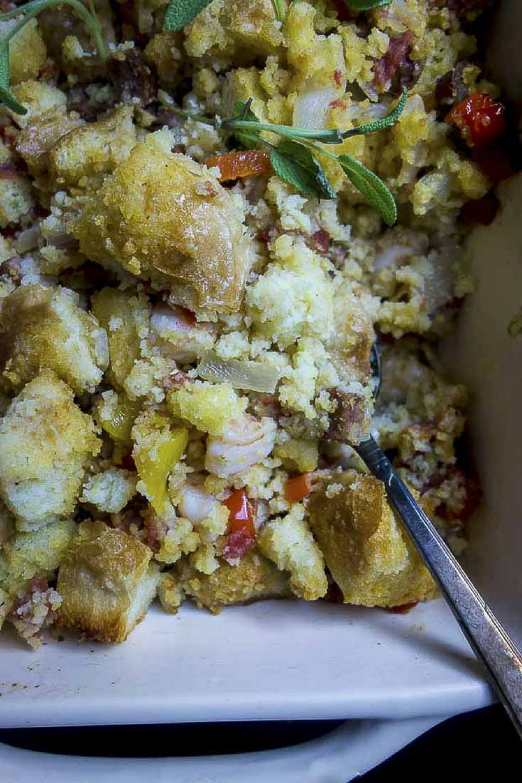 This spicy Jambalaya cornbread stuffing recipe is life with it's buttery, crispy edges, sweet cornbread, spicy andouille sausage, succulent shrimp and Cajun seasonings. You're going to want this at your Thanksgiving dinner! #jambalaya #sausagestuffing #thanksgivingrecipescajun stuffing | shrimp and sausage stuffing | cornbread stuffing | french bread stuffing | Thanksgiving stuffing | how to make stuffing | sausage stuffing | southern cornbread dressing